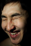 Emotional portrait. The young Asian guy blindly, laughs, an obverse portrait Stock Image