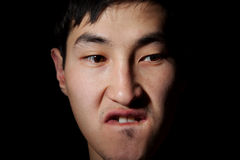 Emotional portrait. The obverse portrait of the young Asian man which poses a mug Royalty Free Stock Photo