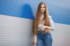 Emotional portrait of a adult pretty blonde woman with gorgeous extra long hair posing outdoors against blue grey striped metal ba Stock Images