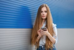 Emotional portrait of a adult pretty blonde woman with gorgeous extra long hair posing outdoors against blue grey striped metal ba Stock Photos