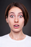 Emotional portrait of amazed woman. Over dark background Royalty Free Stock Photography