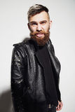 Emotional portrait of a bearded young man in a leather jacket Royalty Free Stock Photos