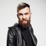 Emotional portrait of a bearded young man in a leather jacket in the studio Royalty Free Stock Image