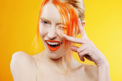 Emotional portrait of beautiful girl with orange hair on orange background Royalty Free Stock Image