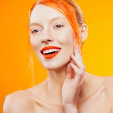 Emotional portrait of beautiful girl with orange hair on orazhevy background Stock Photography