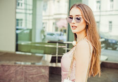 Emotional portrait of a beautiful young brunette woman with long hair in a fashionable dress and sunglasses Royalty Free Stock Photography