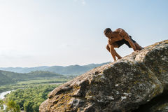 Emotional portrait of black african american man bodybuilder posing on the rock with blue sky background. Wild nature Stock Photography