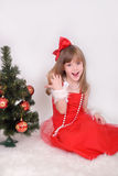 Emotional portrait of a cheerful girl in red dress. New Year's gift under the tree. Emotional portrait of a cheerful girl in red dress Stock Photo