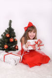 Emotional portrait of a cheerful girl in red dress. New Year's gift under the tree Stock Photo