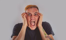 Emotional portrait of a crazy guy in close-up. Concept: the nervous breakdown, mental disease, headaches and migraine stock photo