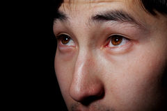 Emotional portrait - eyes. The young Asian guy looks upwards, an obverse portrait Stock Photography