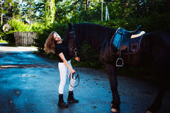 Emotional Portrait of a female in love with horses, black Friesian stallion thoroughbred pet stock photography