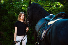 Emotional Portrait of a female in love with horses, black Friesian stallion thoroughbred pet. Emotional  Portrait of a female in love with horses, black Friesian Royalty Free Stock Photo