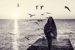 Emotional portrait of girl on pier. Beautiful brunette in plaid meets dawn at sea. Autumn seascape. Flock of seagulls flying in air on sunny morning. Peace and Royalty Free Stock Image