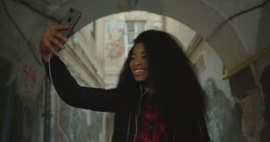 Emotional portrait of the happy attractive yo ung african girl with curly hair taking selfies via the mobile phone. Ourdoor. 4k footage stock footage