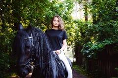 Emotional portrait of a horsewoman rider woman, black Friesian stallion thoroughbred pet