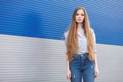 Free Emotional Portrait Of A Adult Pretty Blonde Woman With Gorgeous Extra Long Hair Posing Outdoors Against Blue Grey Striped Metal Ba Stock Images - 100127454