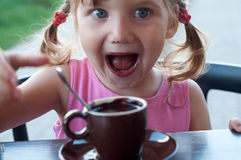 An emotional portrait of a smiling little girl with a cup of hot chocolate Royalty Free Stock Image