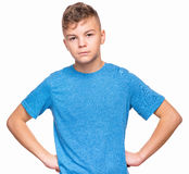 Emotional portrait of teen boy. Confident teen boy posing with hands on his waist. Mad angry handsome young male with hand on hips, isolated on white background Royalty Free Stock Photography