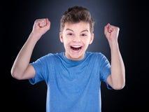 Emotional portrait of teen boy. Half-length emotional portrait of caucasian teen boy. Victory screaming teenager wearing blue t-shirt on black background. Funny Stock Images