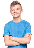 Emotional portrait of teen boy. Half-length emotional portrait of caucasian teen boy wearing blue t-shirt. Funny teenager with arms folded, isolated on white Stock Images