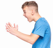 Emotional portrait of teen boy. Profile of the shouting boy - emotional portrait of caucasian teen boy wearing blue t-shirt. Furious teenager screaming with Stock Photos