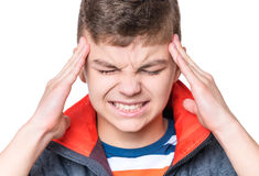Emotional portrait of teen boy. Stress and headache - teen boy having migraine pain. Handsome child suffering from a headache. Unhappy caucasian teenager Stock Photography