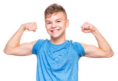 Emotional portrait of teen boy. Thin caucasian teen boy wearing blue t-shirt showing off his biceps. Happy teenager showing his hand biceps muscles strength Stock Photos