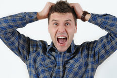 Emotional portrait of young angry screaming man pulling his hair Stock Photo