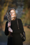 Emotional portrait of young happy beautiful woman with a bouquet of pussy-willows wearing black coat posing on city park at evenin Stock Image