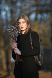 Emotional portrait of young happy beautiful woman with a bouquet of pussy-willows wearing black coat posing on city park at evenin Stock Photography