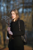 Emotional portrait of young happy beautiful woman with a bouquet of pussy-willows wearing black coat posing on city park at evenin Stock Images