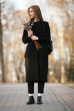 Emotional portrait of young happy beautiful woman with a bouquet of pussy-willows wearing black coat posing on park path at evenin Royalty Free Stock Images