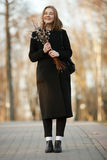Emotional portrait of young happy beautiful woman with a bouquet of pussy-willows wearing black coat posing on park path at evenin Stock Image