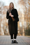 Emotional portrait of young happy beautiful woman with a bouquet of pussy-willows wearing black coat posing on park path at evenin Stock Photography