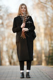 Emotional portrait of young happy beautiful woman with a bouquet of pussy-willows wearing black coat posing on park path at evenin Royalty Free Stock Photography