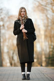 Emotional portrait of young happy beautiful woman with a bouquet of pussy-willows wearing black coat posing on park path at evenin Royalty Free Stock Photos