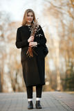 Emotional portrait of young happy beautiful woman with a bouquet of pussy-willows wearing black coat posing on park path at evenin Stock Images