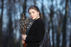 Emotional portrait of young happy beautiful woman with a bouquet of pussy-willows wearing black coat strolling at evening golden h Royalty Free Stock Photo