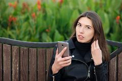 Emotional portrait of a young pretty brunette woman sitting outdoors city park wearing black leather coat using smartphone app for Stock Image