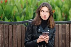 Emotional portrait of a young pretty frustrated brunette woman sitting outdoors city park wearing black leather coat using smartph Royalty Free Stock Images