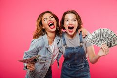 Emotional pretty two women friends holding money. Picture of emotional pretty two women friends holding money isolated over pink background. Looking camera royalty free stock photos