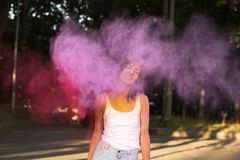 Emotional young woman with short hair posing with exploding Holi Royalty Free Stock Photos