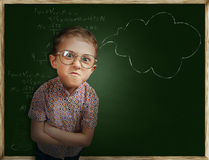 Emotional pupil boy near chalkboard Royalty Free Stock Image