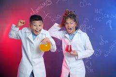 Emotional pupils holding flasks against blackboard stock photography