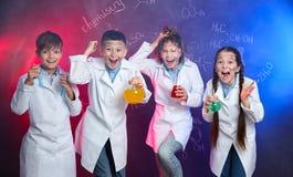 Emotional pupils holding flasks against blackboard with formulas royalty free stock images