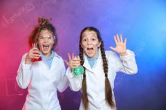 Emotional pupils holding flasks in smoke against blackboard with formulas royalty free stock photo