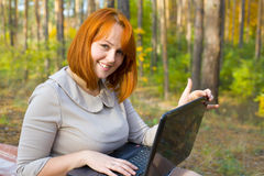 Emotional red-haired girl with the laptop Stock Photos