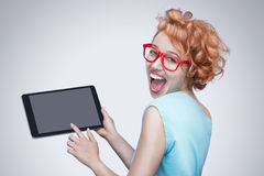 Emotional red-haired girl with red glasses holding and  touching tablet computer. Royalty Free Stock Photos