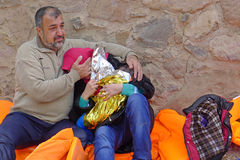 Emotional refugee family Lesvos Greece. Lesvos, Greece- October 20, 2015. Refugee migrants, arrived on Lesvos in inflatable dinghy boats, they stay in refugee royalty free stock photos